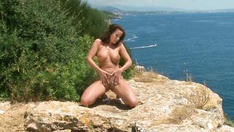 Ослепительная девка ласкает изящное тело позируя голой на обрыве