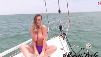 Обольстительная телочка показывает большие дойки на корме яхты